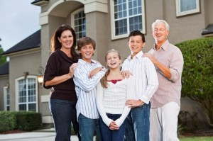 Family of five standing in front of home.  Children - 11 to 14 years.  Parents - 40s.