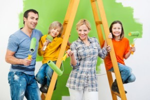 Happy family painting wall in green.