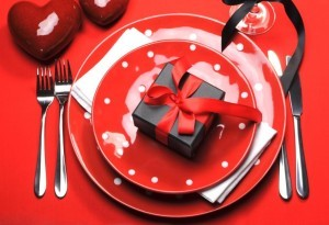 Modern red Valentine romantic table setting with red polka dot plates on bright red tablecloth with black box present  gift.