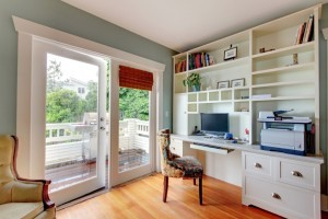 Home office with green walls and white shelves